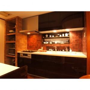 オーブンを置くスペースをご希望され、キッチンの奥行にあわせオープン棚を造りつけました。(向かって左側) レンガ風のタイル貼りで暖炉のような暖かいイメージです。 また、正面の引違窓を横すべり窓に変更し、下部には洗剤などの 収納棚を造りました。